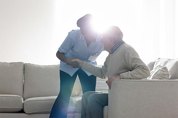 mujer ayuda a levantarse a un anciano