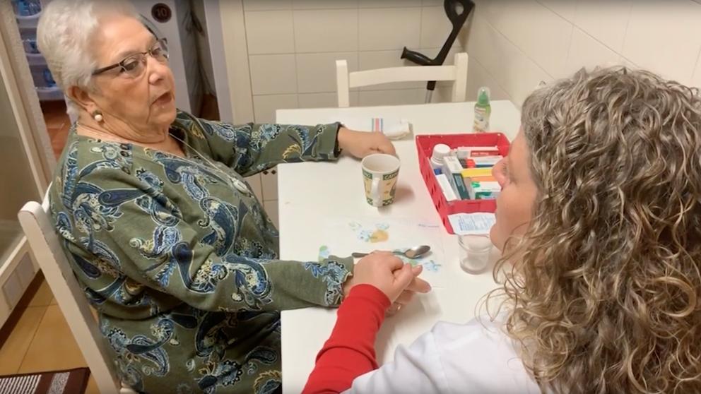 mujer mayor con cuidadora tomando su medicación