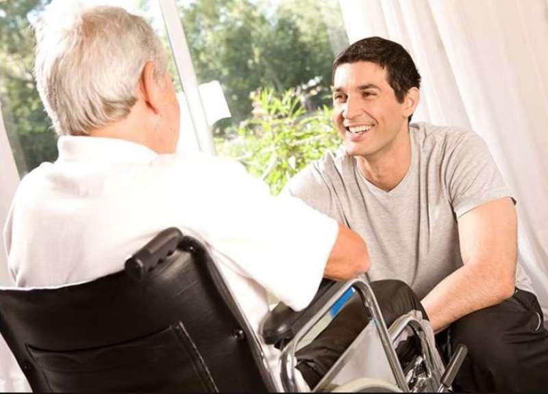 anciano en silla de ruedas hablando con joven sonriente