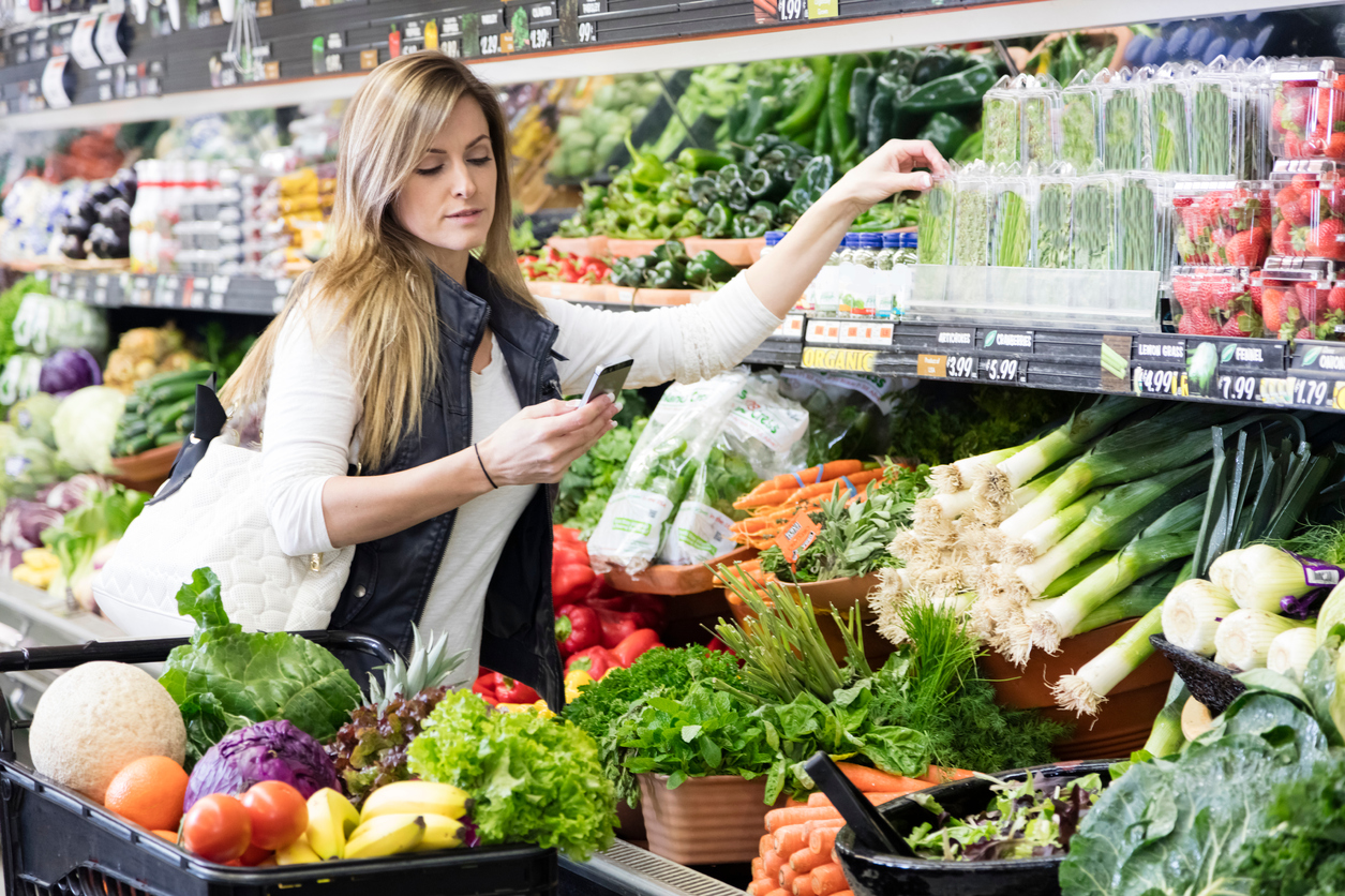 Woman with cart shopping in grocery store in the produce section. Using smart phone